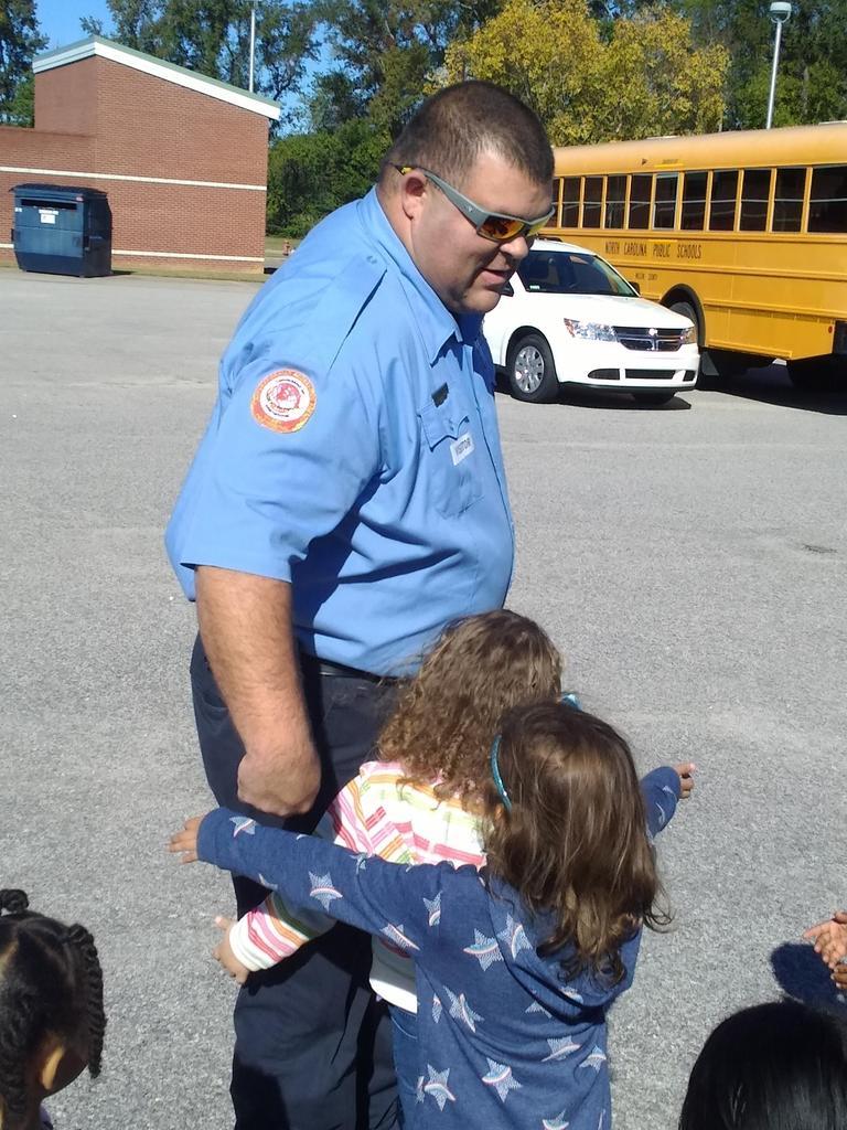 Firefighter hugs students.
