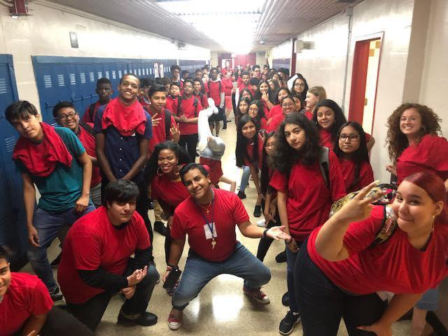 large group of students dressed in red in hallway