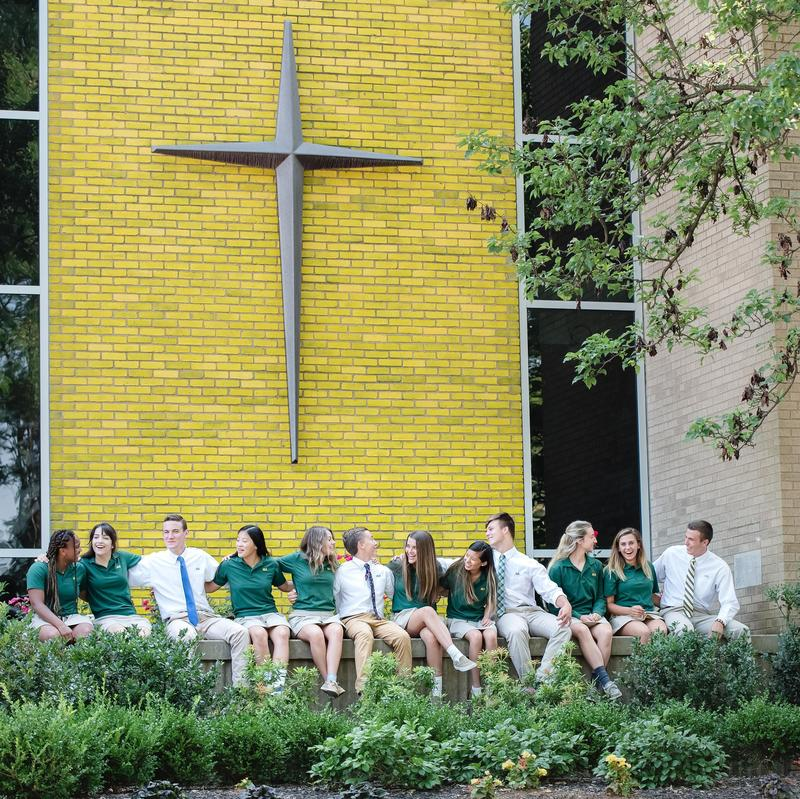 students sitting on front wall