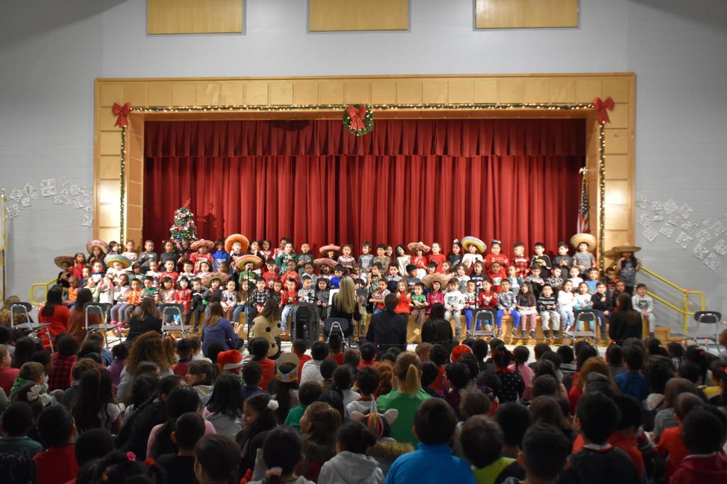 A stage filled with young students, many of whom are wearing sombrero hats