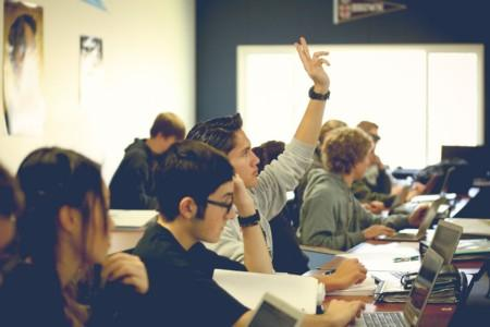 Student raising his hand in class.