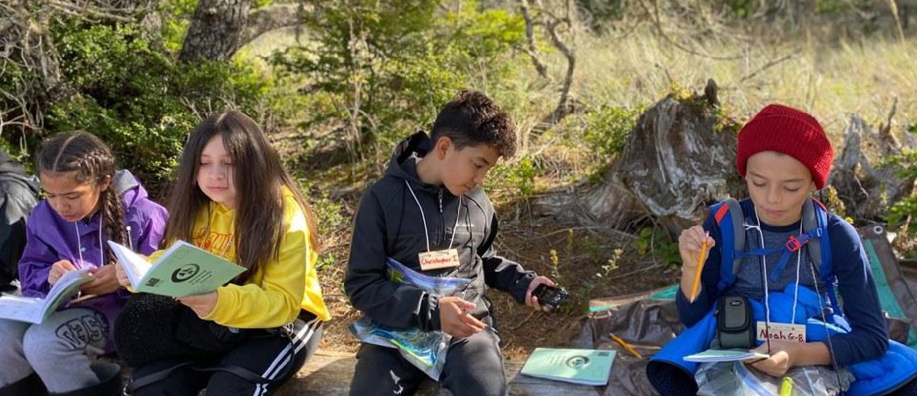 Four students sitting on a log at Outdoor School while recording notes in their journals