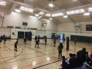 two volleyball teams playing on a volleyball court