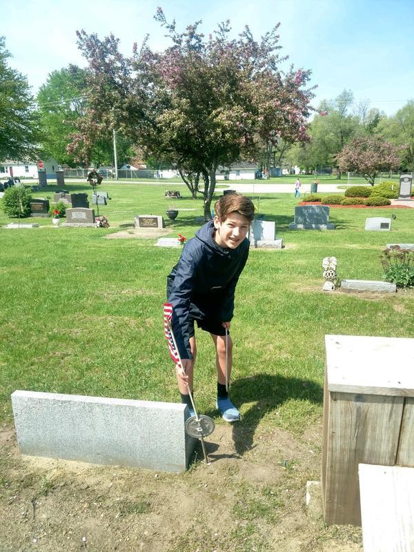 Daniel Beyer places a flag at a grave site.