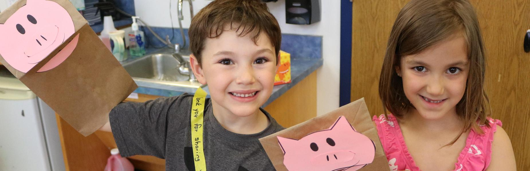 Two kindergartners hold handmade Elephant & Piggy puppets.