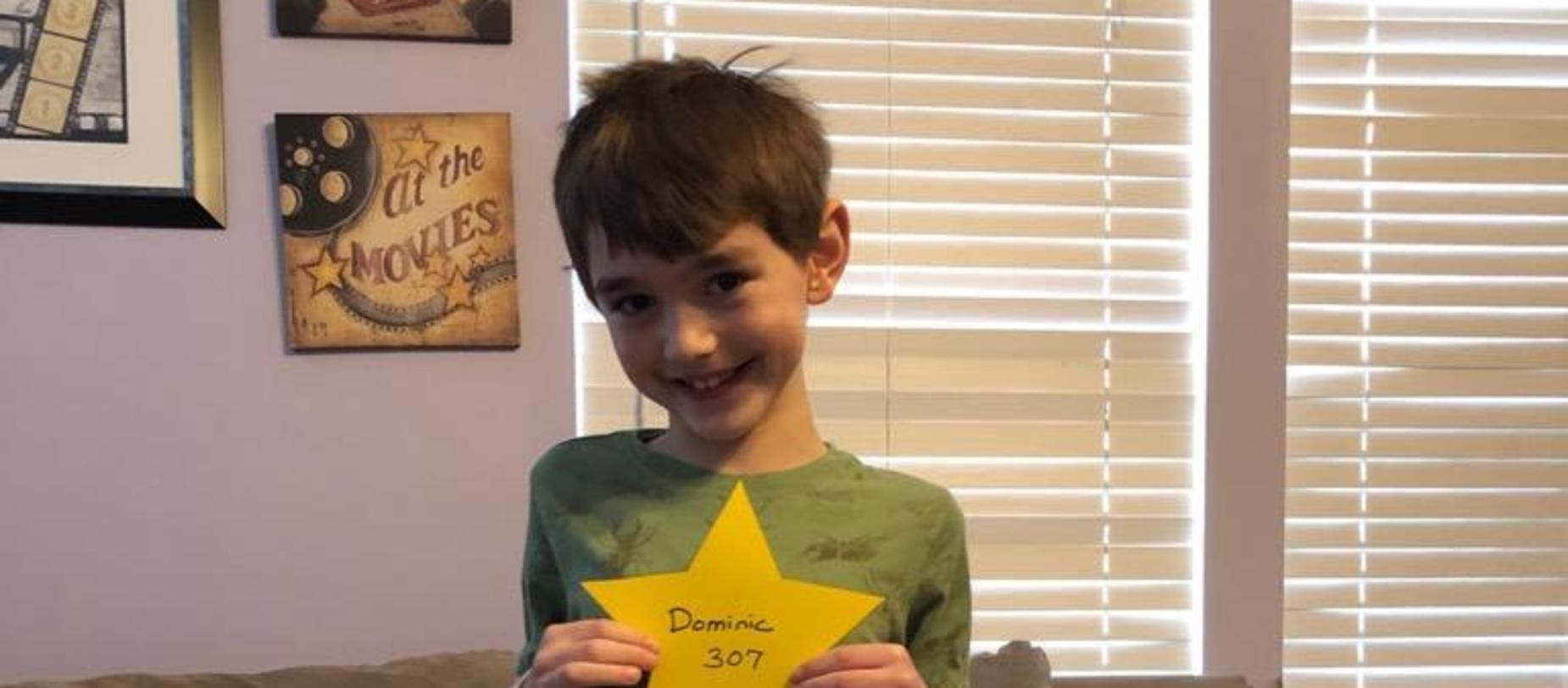 boy holding a star smiling for camera