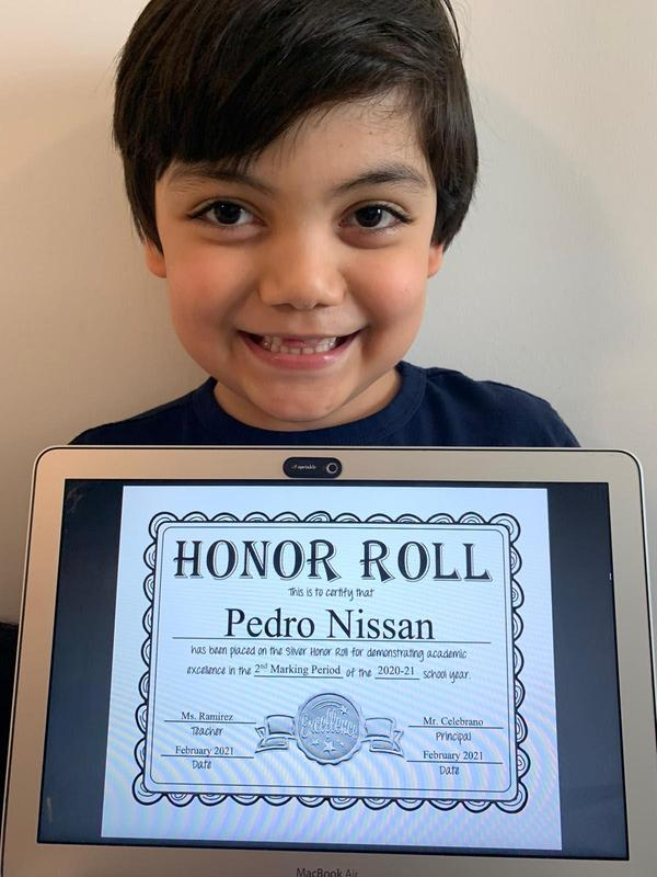 Pedro holding honor roll certificate