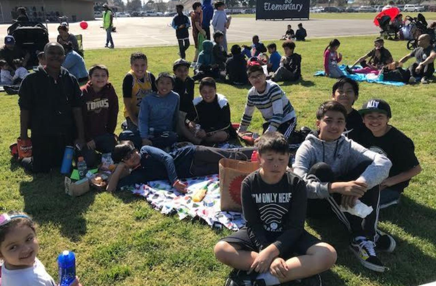 male students sitting on grass having a picnic