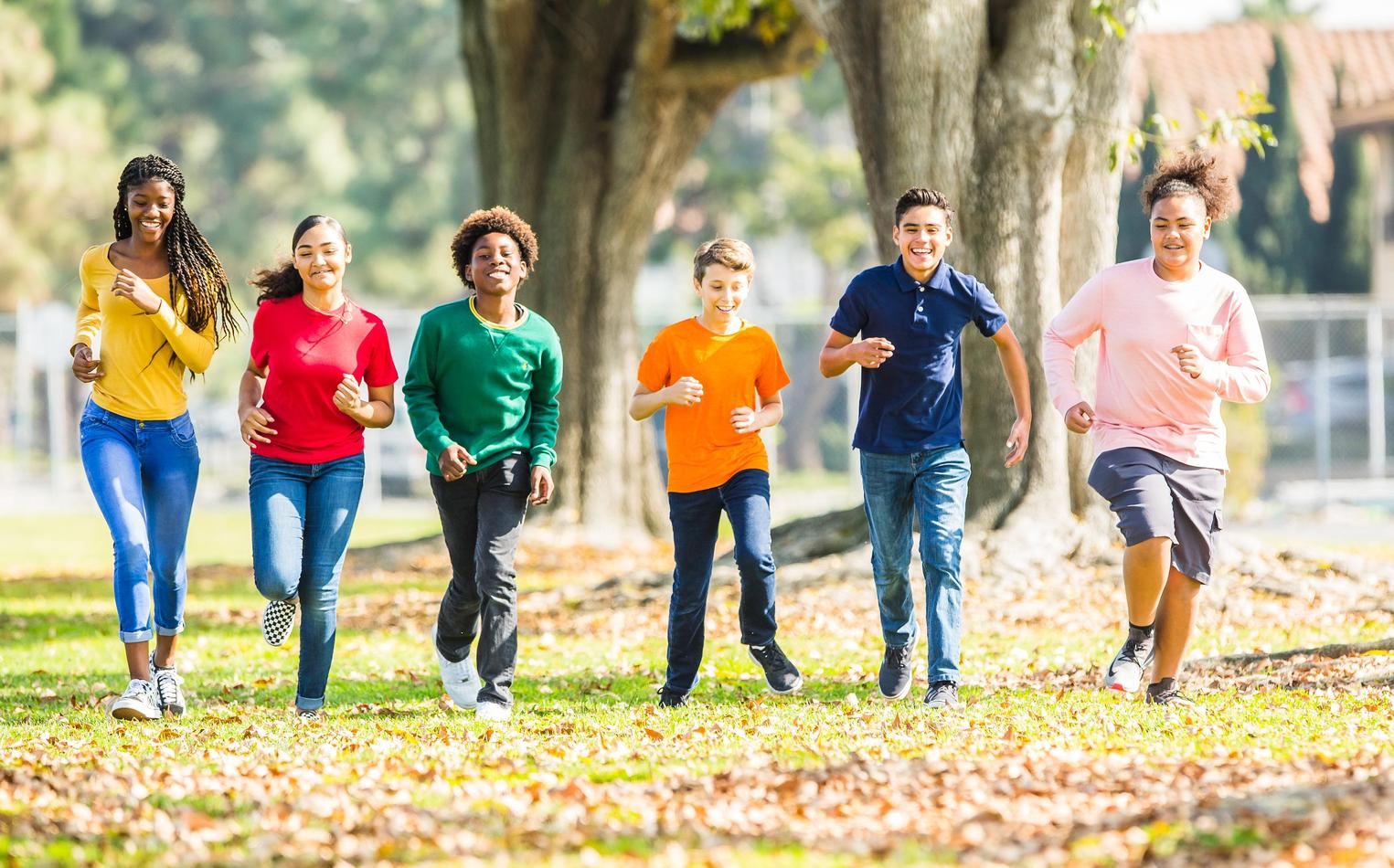 A group of middle school students running on a field covered with fallen leaves.