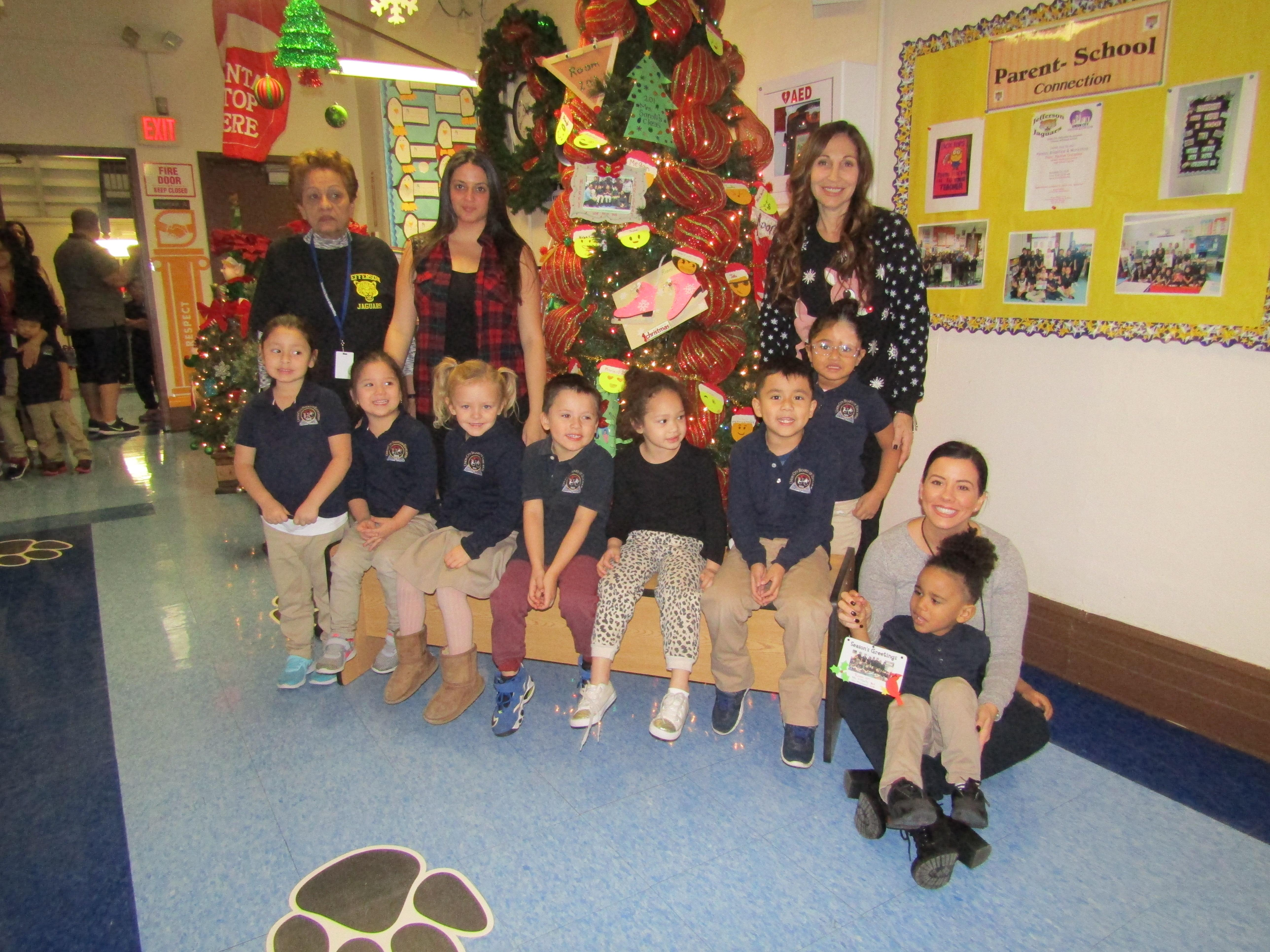 pre-k class with teacher and aides in front of the christmas tree