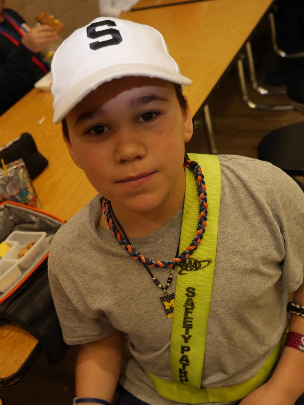 student in safety patrol gear poses for camera