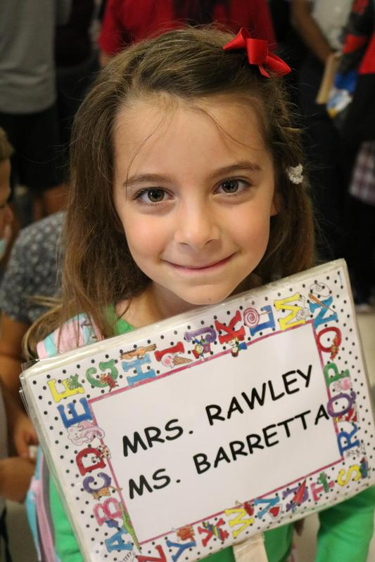 Photo of kindergartner holding sign with teacher names on first day of school.
