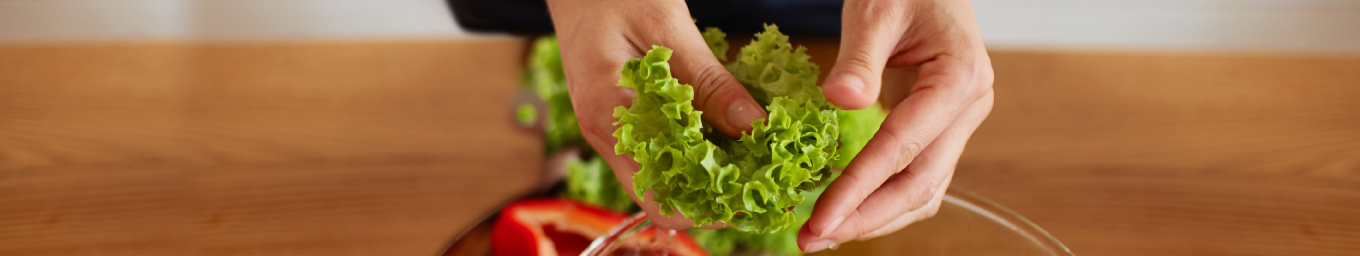 Hands holding salad in shape of heart