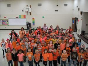 Students and staff members wear orange.