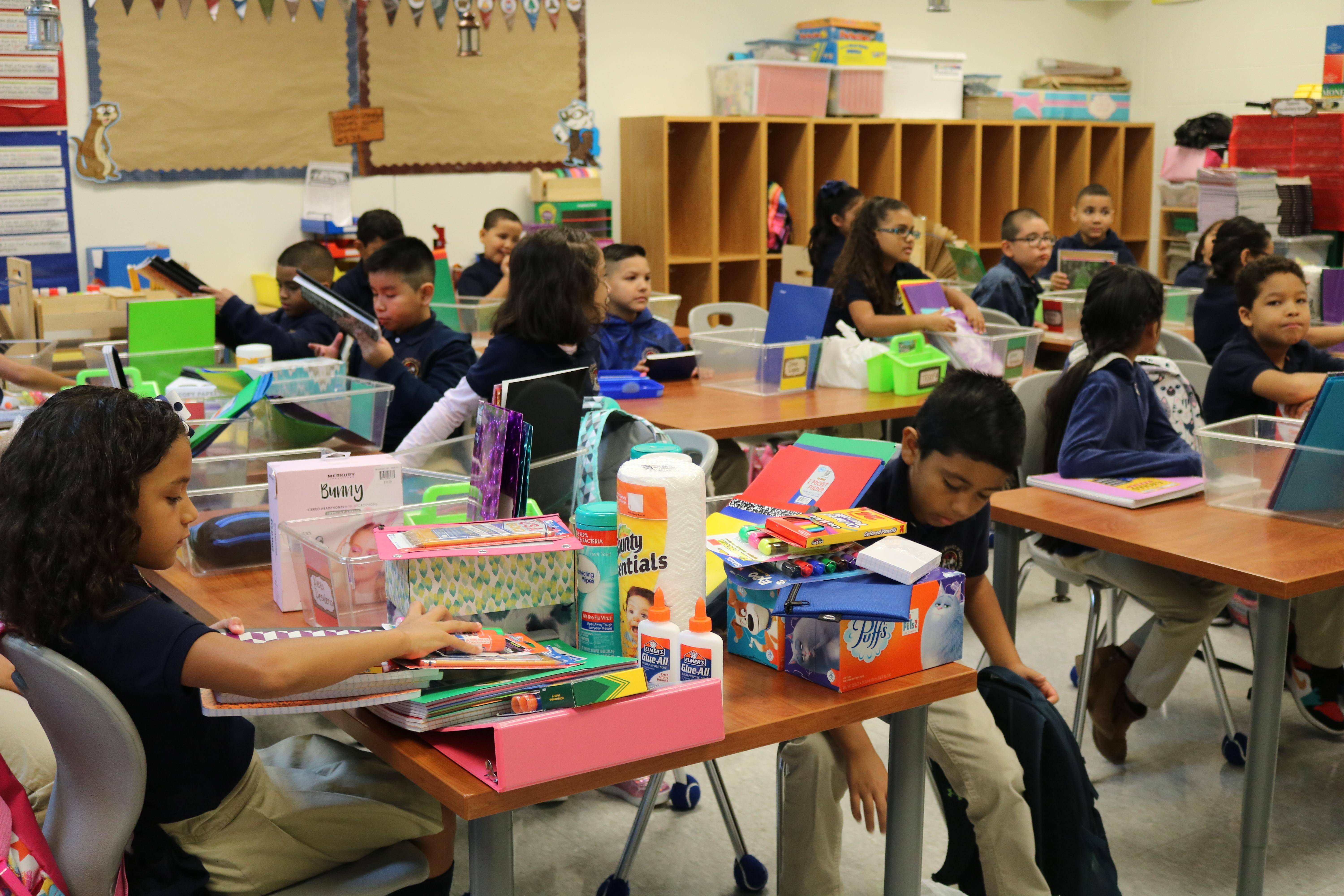 students sitting in class with their supplies