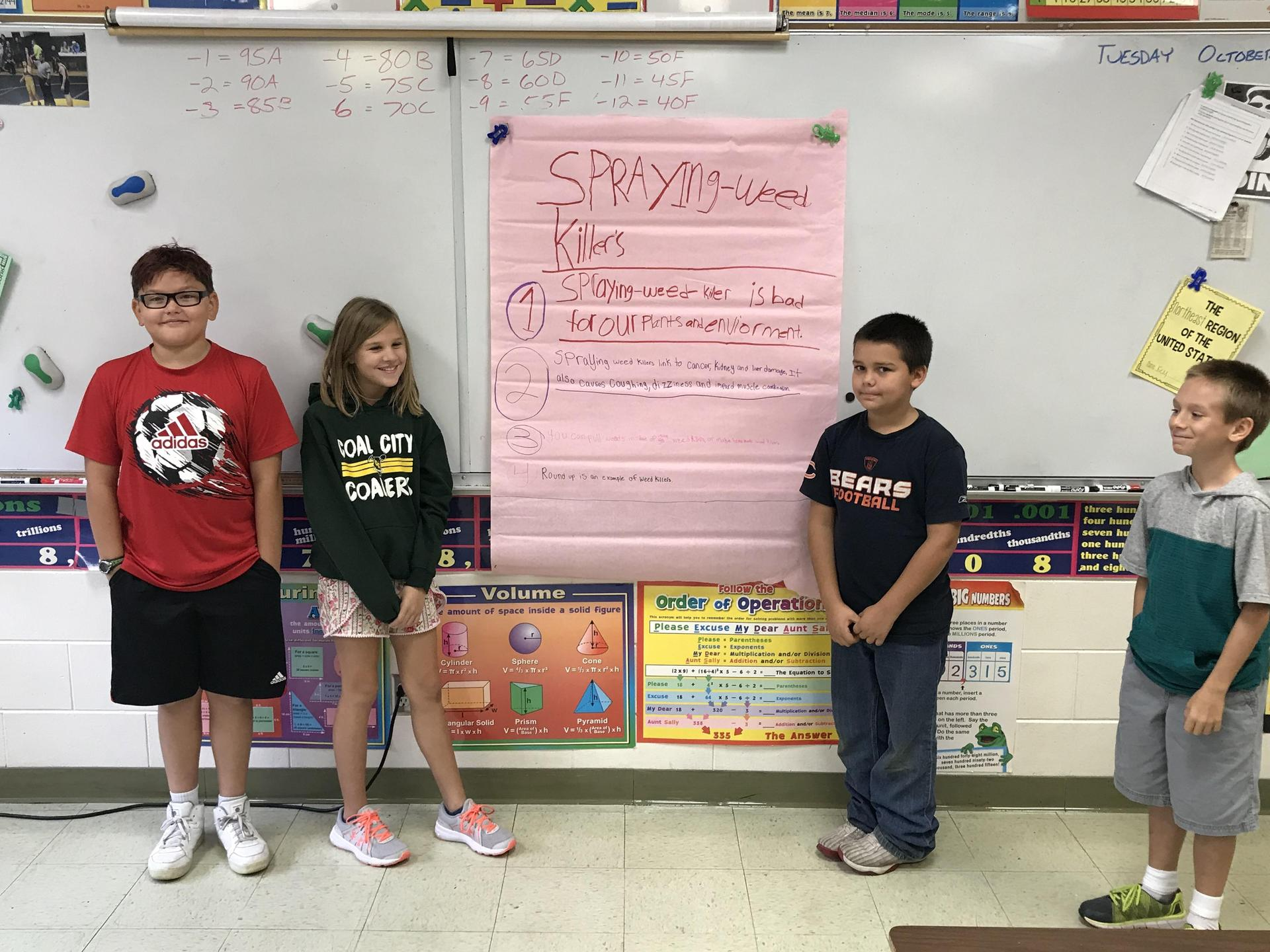 Students model their Science poster