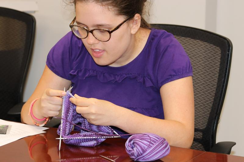 Young lady knitting with pretty purple yarn