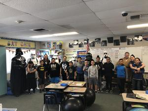 Students and staff stand with Star Wars costumed characters.