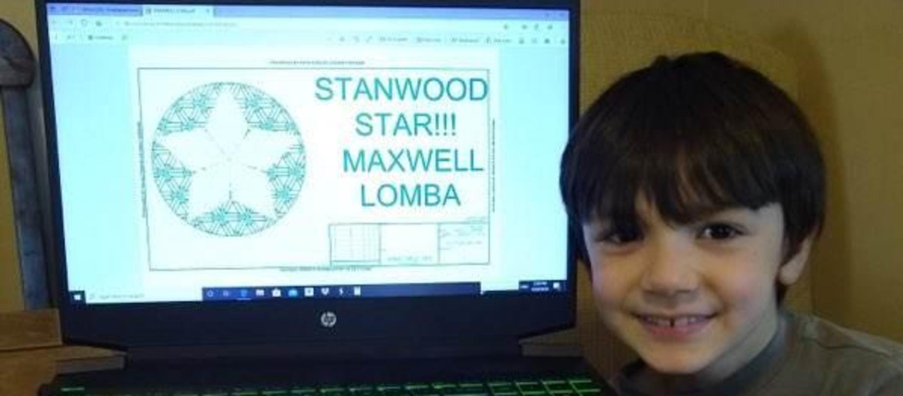 boy sitting beside his computer showing he got a star from his school