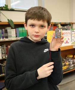 A 6th grader at Roosevelt Intermediate School, displays a wireless micro:bit he programmed to create an LED coded design, one of many Hour of Code activities taking place in Westfield Public Schools during Computer Science Education Week.