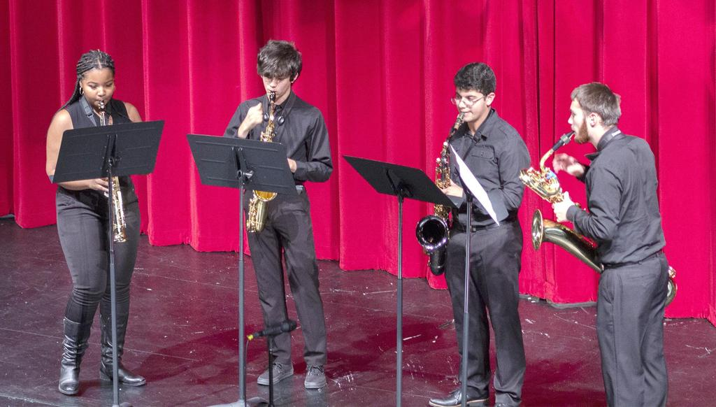 A quartet featuring a sax player and three trumpet players
