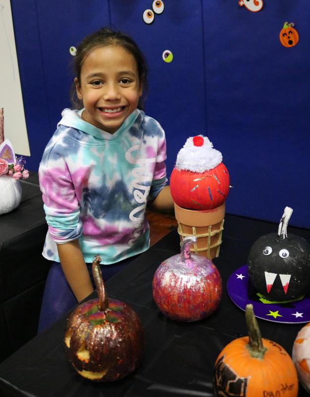 Student poses in front of her creative decorated pumpkin at Wilson School's Pumpkin Patch.