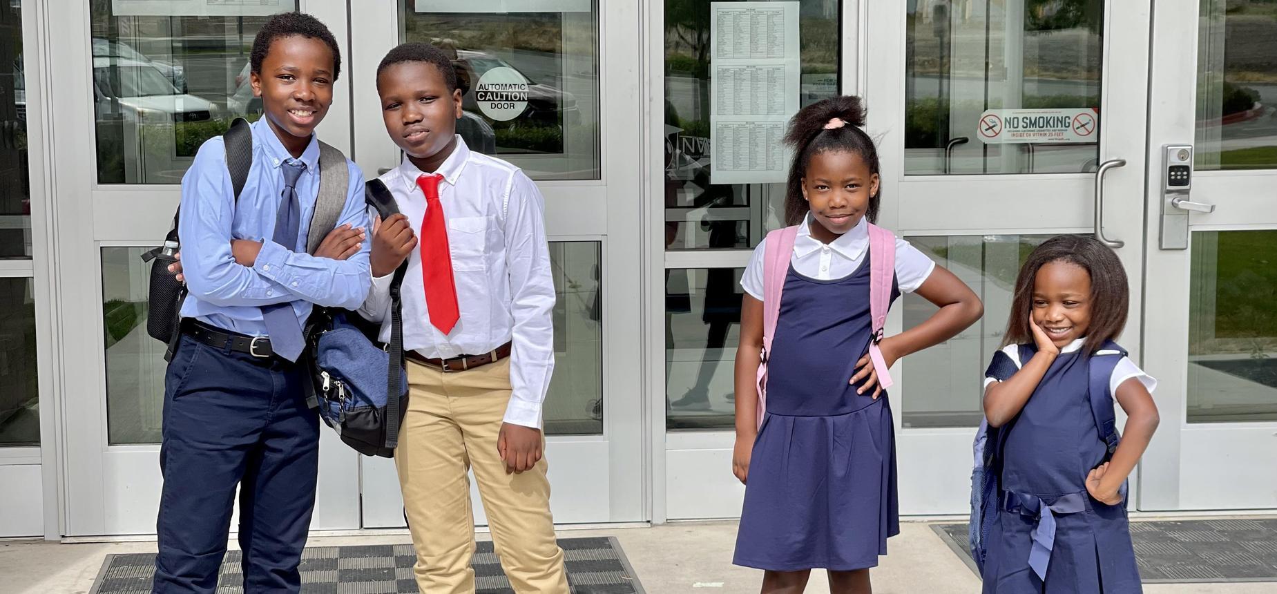 Children with backpacks in blue uniforms standing in front of school Legacy Prep best charter school in Davis School District