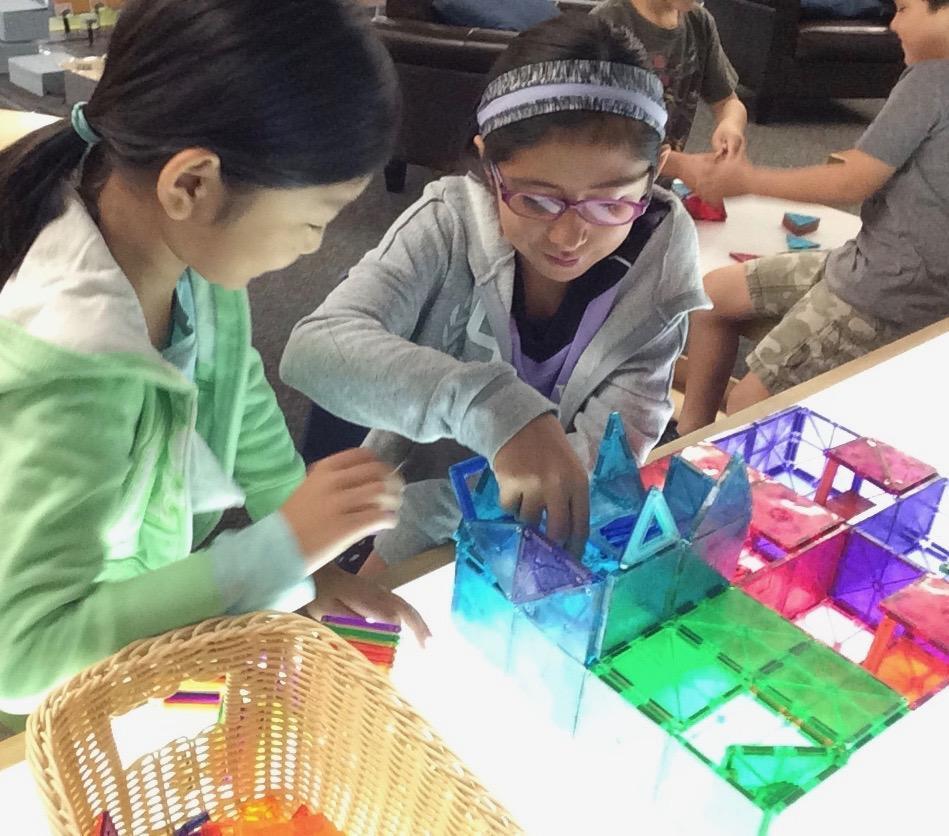 Children exploring magnet tiles on a light table building a structure.