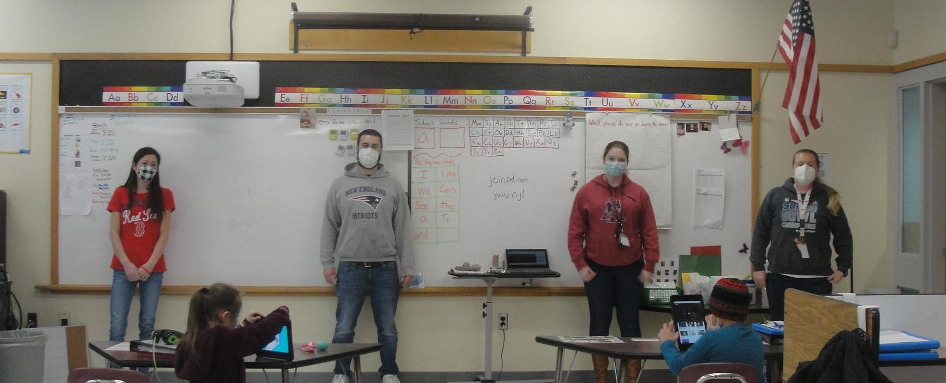 Staff stands socially distanced with masks in a class