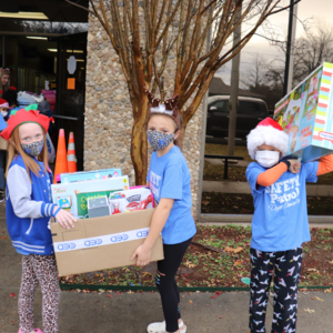 dyer students work together to carry toys inside the school