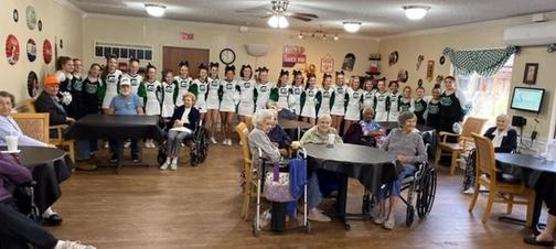 a picture of cheer and dance teams visiting nursing home