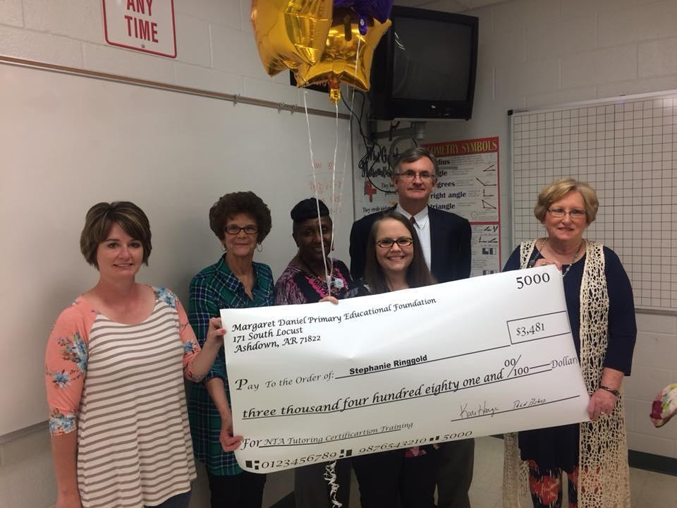 AHS staff members holding a check
