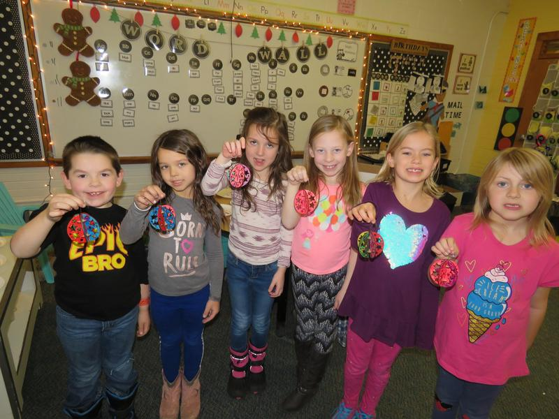 First graders proudly display their finished ornaments.