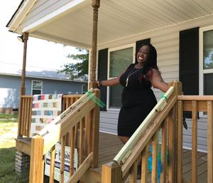 Jamecia Oliver at her new home, whose walls were built by Lexington Two students