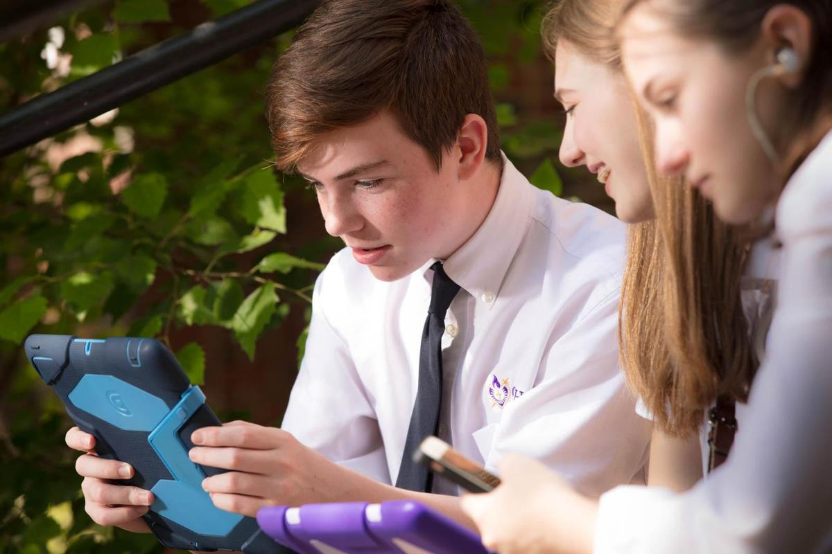 photo of a boy and two girls looking at iPads