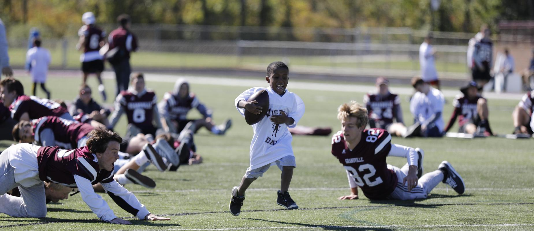 boy running with ball by football players on field
