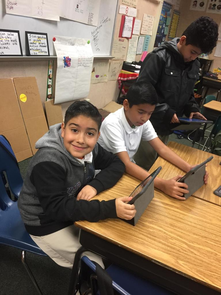 students pose for a picture while working on iPads