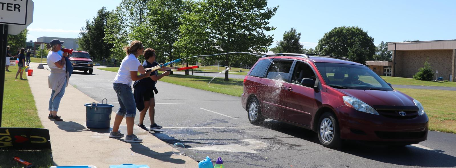 a car gets sprayed with a super soaker during the end of the year parade