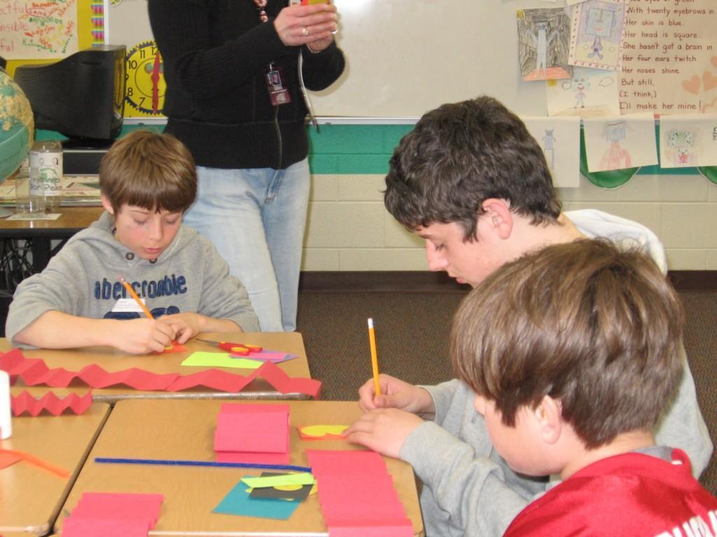 students create paper crafts at desks