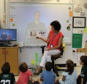 Photo of kindergarten teacher reading to her class.