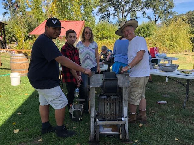 Ed Nickerman and students pressing aples at the Apple Farm Field Trip/