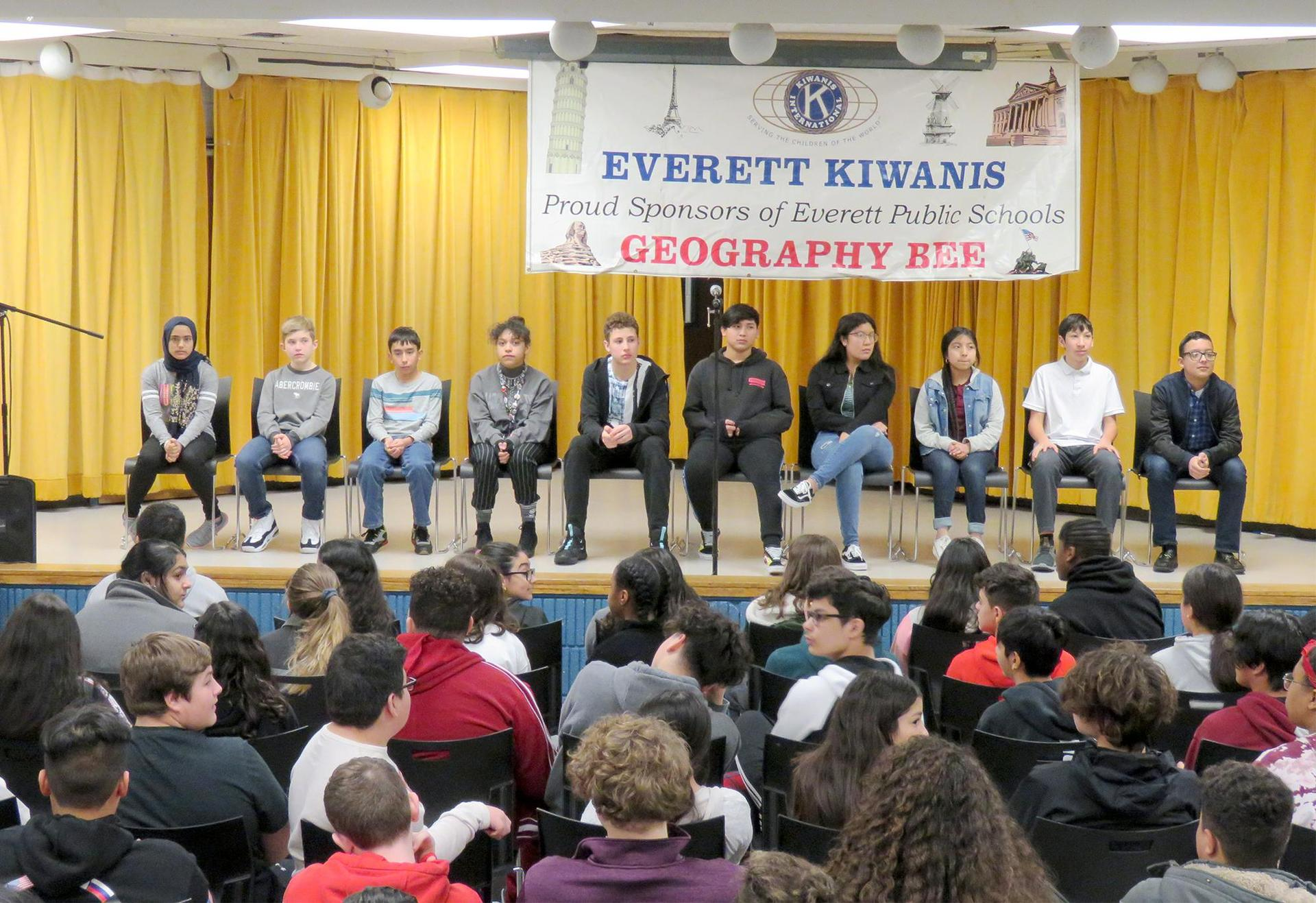 Geography Bee contestants take their seats on stage