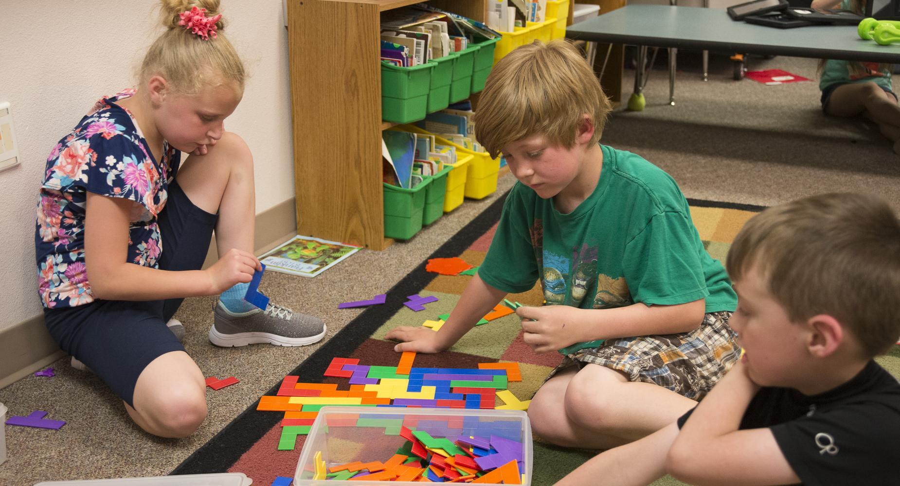 Students play with shape blocks on the carpet.
