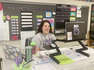 the image is of a teacher wearing a grey shirt sitting at her desk. her laptop is in front of her. she is teaching virtually and smiling.