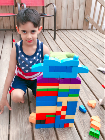 Boy outside on balcony with building block structure