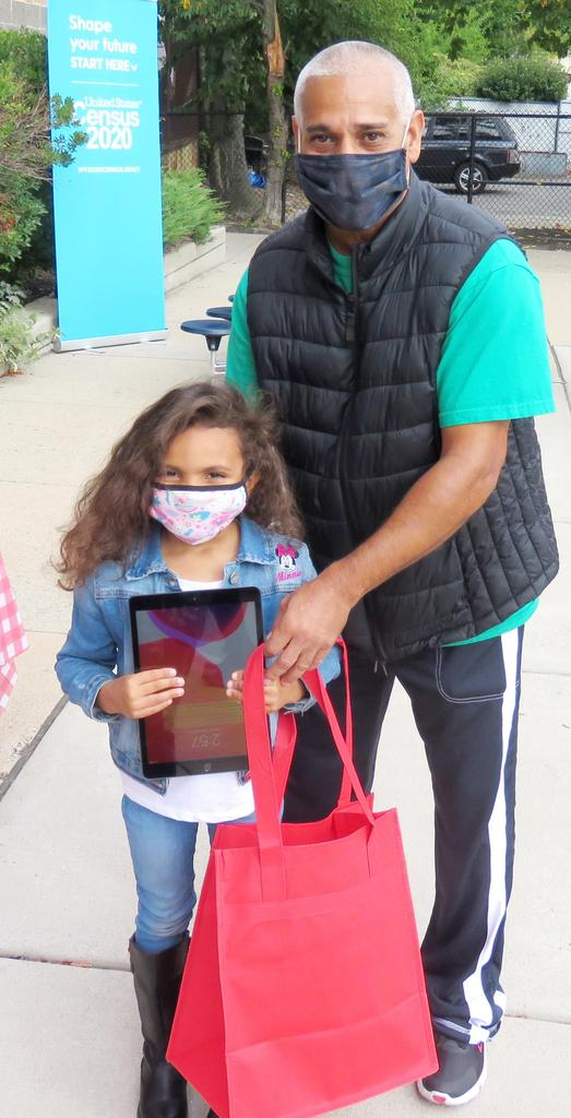 An adult and a young student holding an iPad