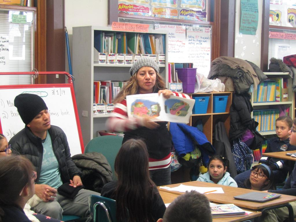 parent reading a book to her child's class