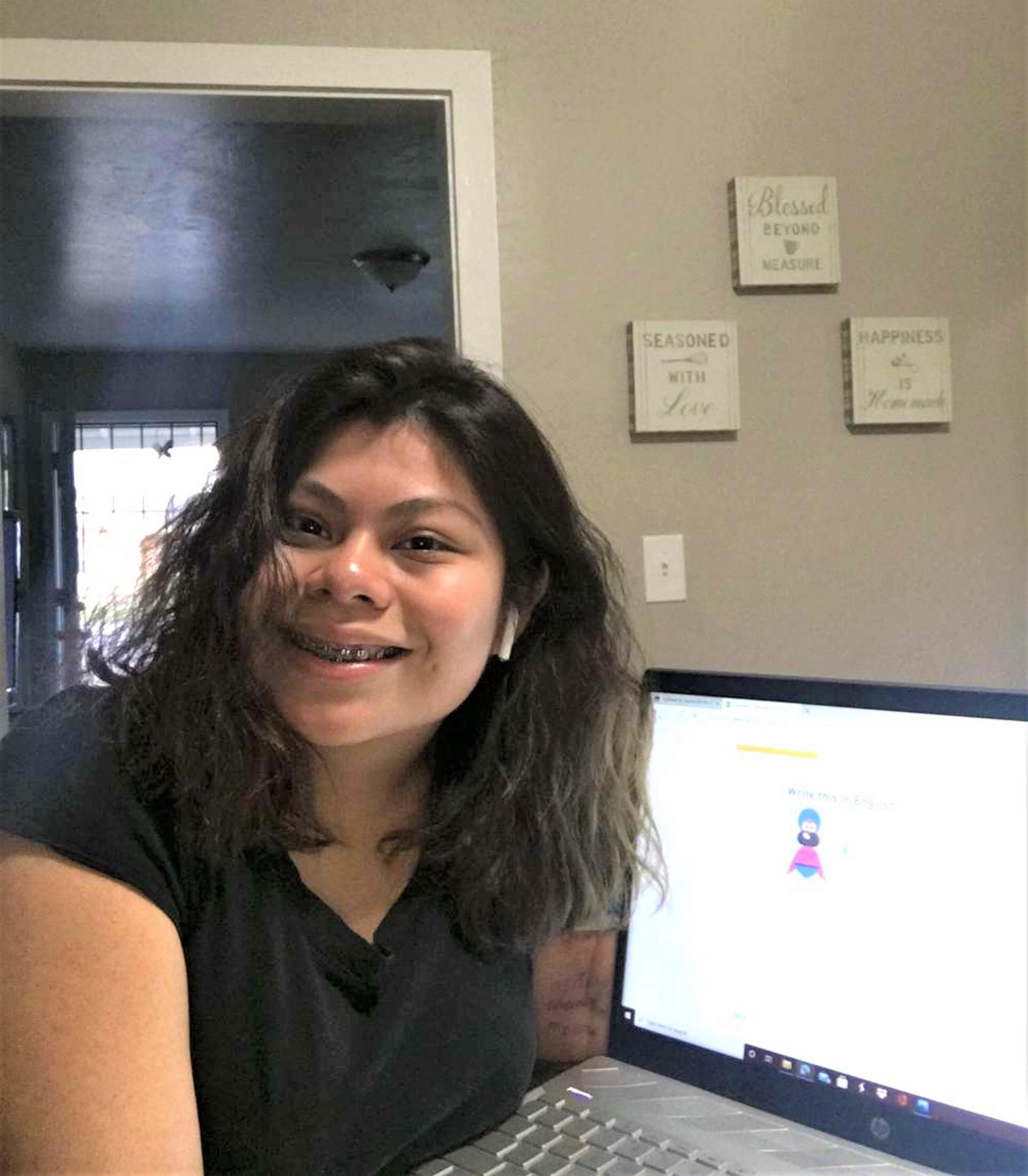 a student posing with their computer in their distance learning workspace