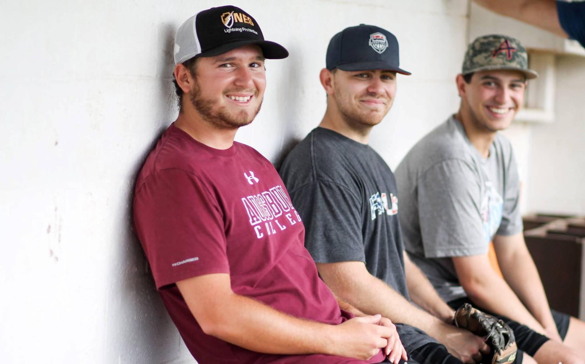 Three alumni smile at camera