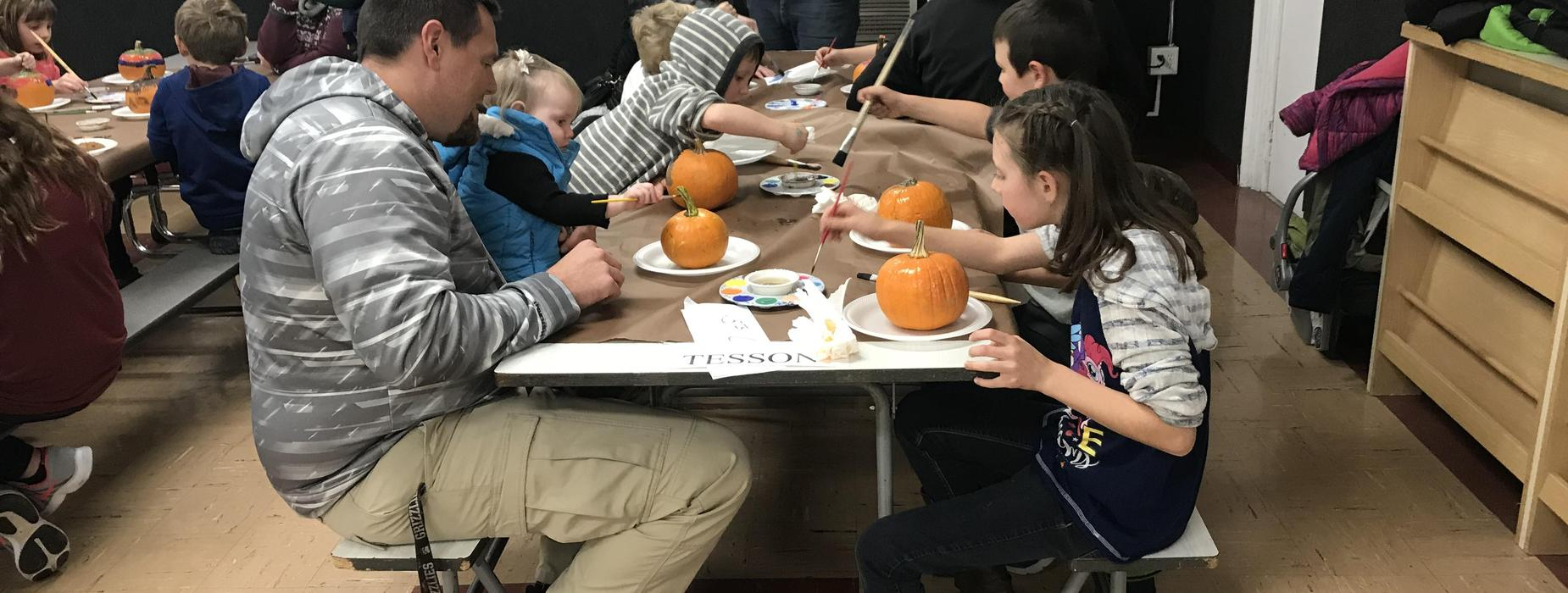 Parents and Students Work on Painting Pumpkins